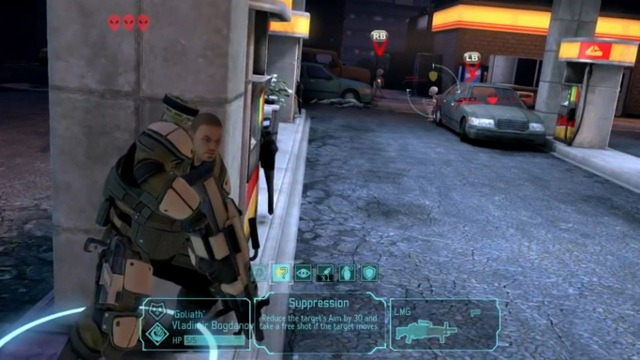 A heavily-armoured X-Com soldier crouches against a concrete pillar in a service-station, ready to receive fire-orders against the two sectoid aliens in the background.